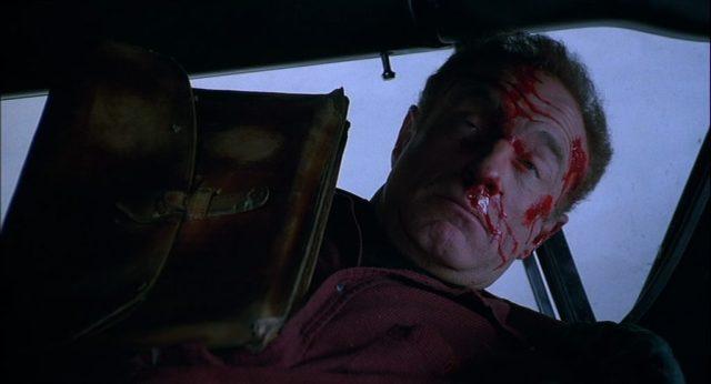 James Caan als Paul Sheldon im verunglückten Fahrzeug mit blutverschmiertem Gesicht und perplexem Blick, neben ihm seine lederne Aktentasche.