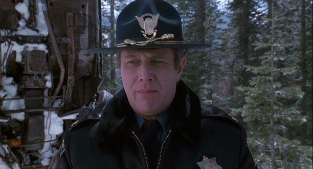 Nahaufnahme von J.T. Walsh als Polizist am Rande eines Waldes in Colorado.
