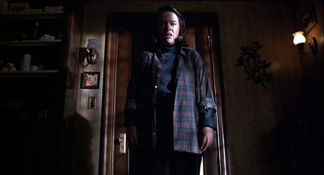 Annie Wilkes aus der Froschperspektive in einem düsteren Raum ihres Hauses.