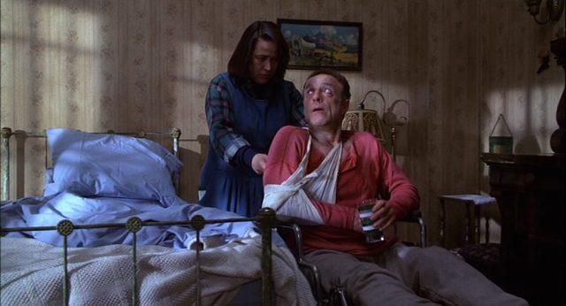 Kathy Bates als Annie Wilkes am Rollstuhl, in dem Sheldon mit seinem Arm in einer Schlinge sitzt.