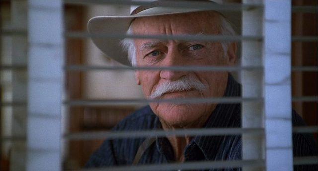 Nahaufnahme von Richard Farnsworth als Kleinstadt-Sheriff Buster, der nachdenklich durch die Lamellen der Jalousie eines Fensters blickt.