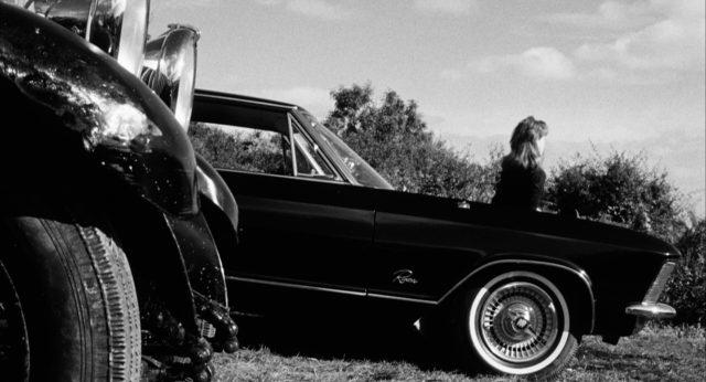 Nahaufnahme von einer nahe dem Strand geparkten Limousine, auf deren Motorhaube Nicola sitzt und Richtung Meer schaut.