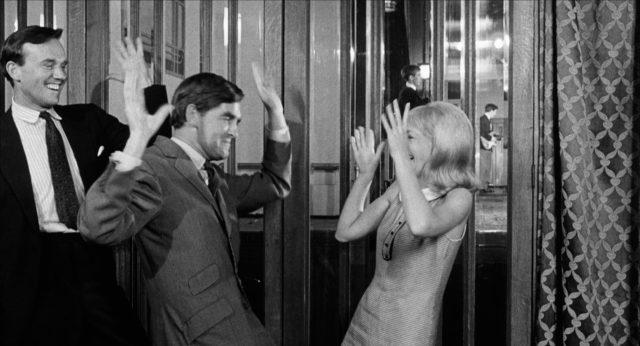Suzy tanzt fröhlich mit zwei Männern in einer Bar.