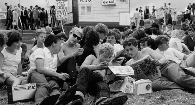 Jugendliche sitzen am Sandstrand.