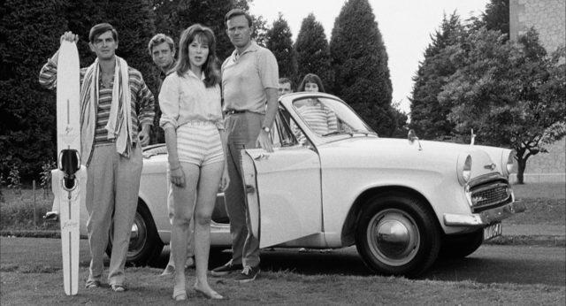 Eine Gruppe von jungen Upperclass-Urlaubern vor ihrem Kleinwagen.