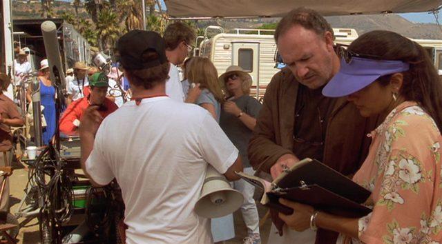 Gene Hackman als Regisseur am Set im Gespräch mit einer Assistentin.