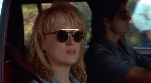 Nahaufnahme von Suzanne mit Sonnenbrille im Auto auf der Beifahrerseite beim Blick durch das Türfenster.