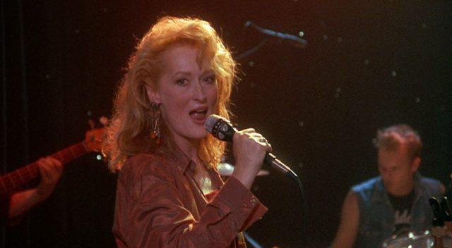 Nahaufnahme von Suzanne bei einer Gesangseinlage mit Mikrofon und Band.