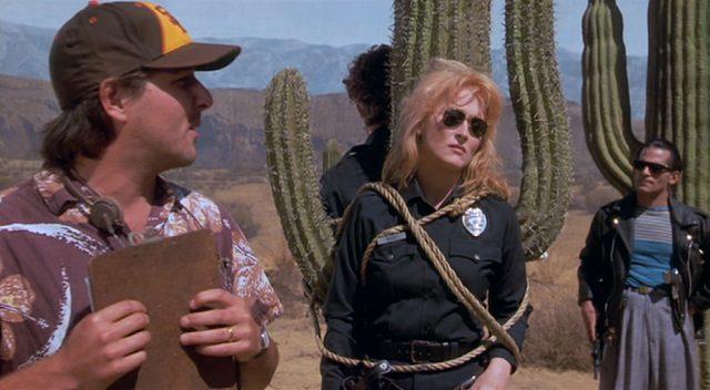 Meryl Streep als Suzanne Vale in Polizeikostüm am Set, festgebunden an einer Kaktus-Requisite; im Vordergrund steht ein Assistent mit Klemmbrett.