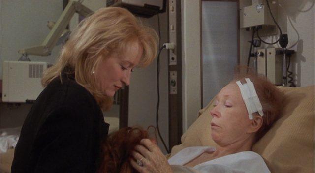 Suzanne am Krankenbett von Doris, die ihre Perücke in den Händen hält.