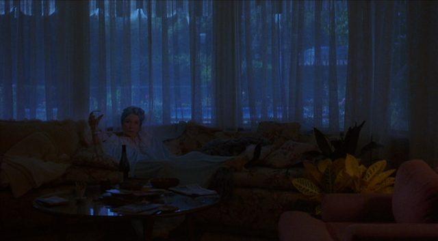 Doris mit Drink und ausgestreckten Beinen auf ihrer Couch in einem depressiv-melancholisch ausgeleuchteten Zimmer.