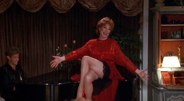 Shirley MacLaine als Doris Mann in rotem Kleid in lasziver Pose auf einem Flügel, an dem ein Mann spielt.