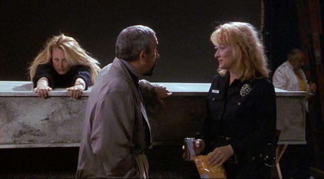 Suzanne Vale am Set im Polizeikostüm im Gespräch mit ihrem Regisseur. Im Hintergrund posiert ihr Stuntdouble.