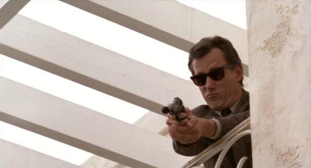 Nahaufnahme von Cleve mit Sonnenbrille und schallgedämpfter Pistole im Anschlag.