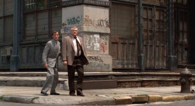 Cleve und Madlock vor einem verlassenen Gebäude an einer Straßenecke.