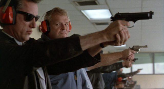Cleve und Meechum am Schießstand; Cleve hat seine Pistole ausgerichtet und trägt eine Sonnenbrille, Meechum beäugt ihn.
