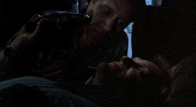 Meechum hält Cleve in einem dunklen Raum im Liegen eine Pistole an die Wange.