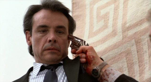 Nahaufnahme von Paul Shenar als Madlock, dem jemand mit blutverschmiertem Ärmel einen Revolver an den Kopf hält.