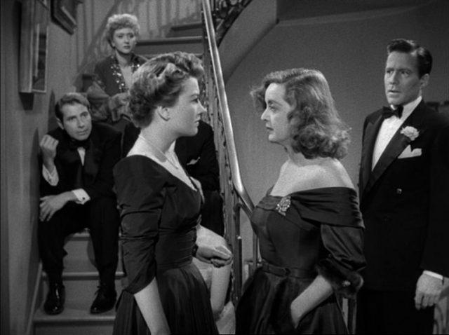 Eve Harrington und Margo Channing stehen sich in konfrontativer Haltung gegenüber.