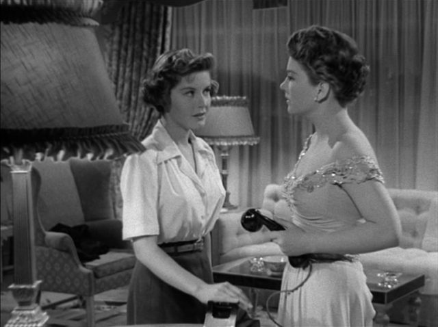 Phoebe, gespielt von Barbara Bates, drückt ihre Hand auf die Telefongabel, während ihr gegenüber Eve mit dem Hörer in der Hand sie anblickt.