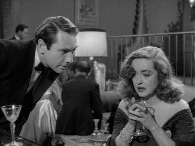 Bill Simpson im Gespräch mit Margo Channing, die in beiden Händen einen Drink hält und deren Gesicht unglücklich wirkt.