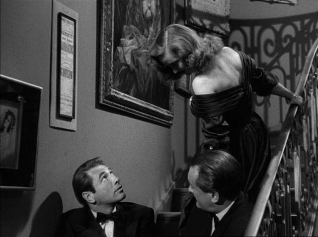 Margo Channing dreht sich am Treppenaufgang zu dem weiter unten sitzenden Bill Simpson (gespielt von Gary Merrill) um.