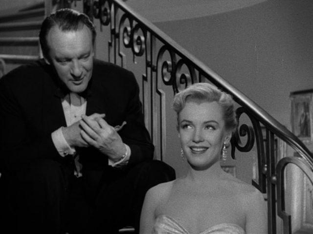 Der Kritiker Addison DeWitt sitzt mit der Nachwuchsschauspielerin Casswell im Gespräch auf den Stufen einer Treppe; Casswell wird von Marilyn Monroe gespielt.