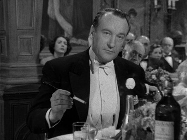 George Sanders als Addison DeWitt im Smoking am Bankett-Tisch; seine Zigarette befindet sich im Zigarettenhalter.