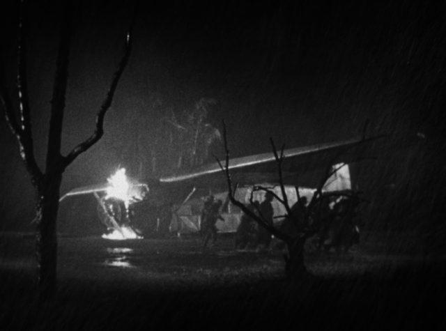 In der Dunkeltheit leuchtet das Feuer des brennenden Motors einer abgestürzten Maschine, während im Vordergrund die Rettungskräfte sich eilig vom Wrack entfernen.