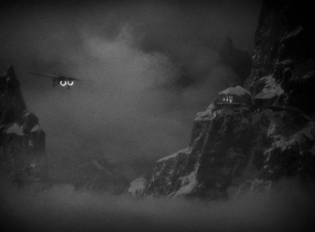 Eine dreimotorige Ford Trimotor fliegt mit zwei brennenden Motoren bei Nacht und Nebel am Ausguckhaus vorbei durch die Andenschlucht.
