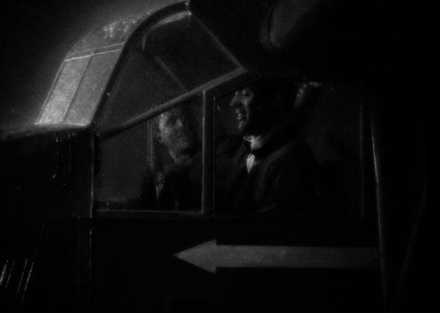 Nahaufnahme bei Nacht von Geoff Carter im Cockpit, auf dessen Scheiben der Regen prasselt.