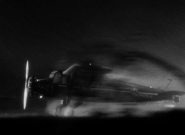 Eine einmotorige TravelAir 6000 prescht bei Dunkelheit über die nasse Startbahn.