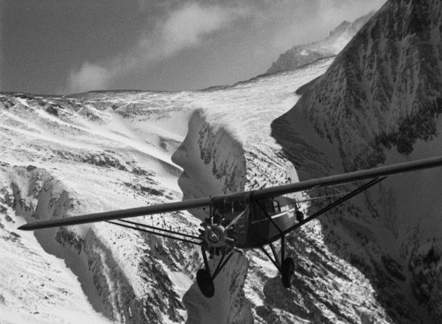 Einmotorige Barranca-Maschine beim Flug vor dem Hintergrund eines verschneiten Gebirges.