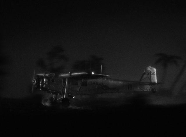 Seitlicher Blick auf ein startendes Flugzeug bei Nacht und Regen; in Wirklichkeit handelt es sich um ein Modellflugzeug.