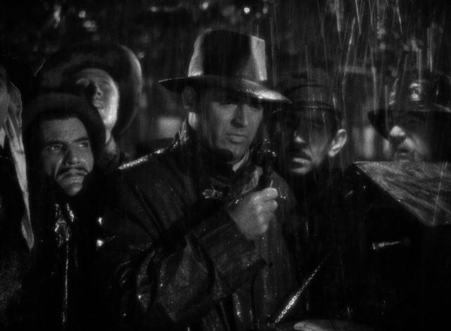 Geoff Carter steht im Beisein einiger Mitarbeiter draußen in strömendem Regen am Funkgerät, alle mit besorgten Mienen.