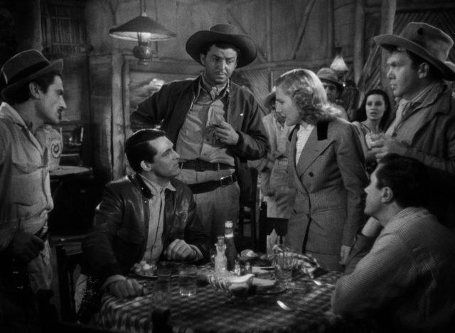 Bonnie konfroniert Geoff, der an einem Bartisch sitzt, im Beisein von einigen Barranca-Beschäftigten.