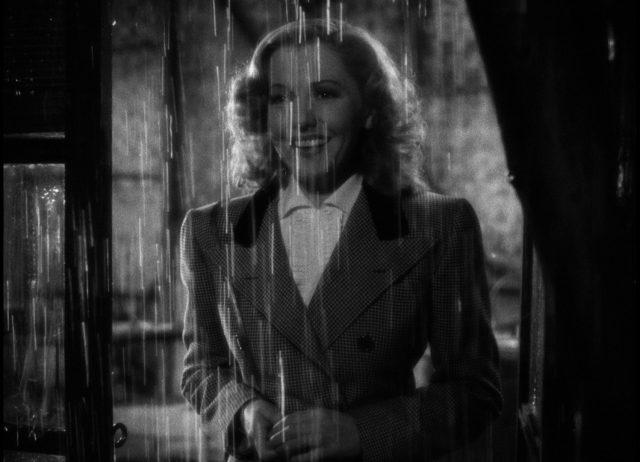 Nahaufnahme von Bonnie, die mit breitem Lächeln in einer Tür steht, während im Vordergrund viele Regentropfen herabfallen.