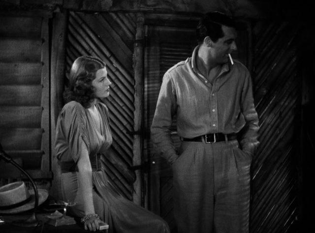 Rita Hayworth als Judy MacPherson sitzt auf einer Tischkante, neben ihr steht Geoff Carter, in dessen Mundwinkel eine Zigarette hängt.