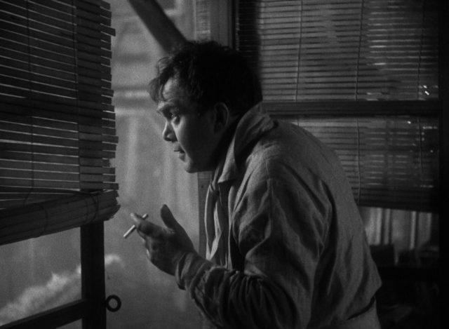 Thomas Mitchell als Kid Dabb, der mit Zigarette in der Hand aus der geöffneten Tür nach draußen schaut.
