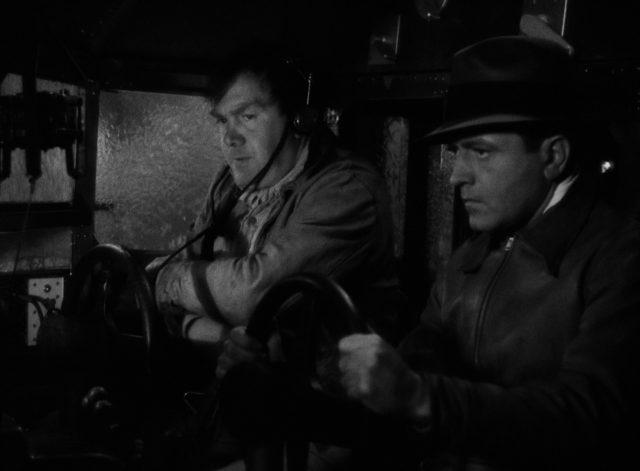Nahaufnahme von Kid und Bat bei riskantem Flug im Cockpit; an den überströmten Scheiben ist der heftige Regen zu erkennen.