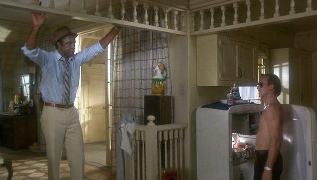 Oscar Grace bei Ned Racine, der mit Sonnenbrille und nacktem Oberkörper am geöffneten Kühlschrank steht.