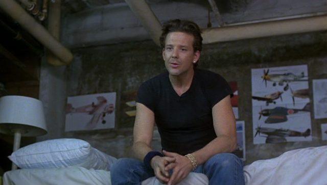 Mickey Rourke als Teddy Lewis mit nachdenklichem Blick auf einem Bett in einer kargen Wohnung.