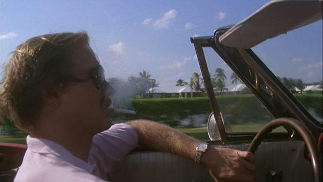 Ned Racine mit rauchender Zigarette am Steuer seines Cabriolets; im Hintergrund Häuser und Palmen.