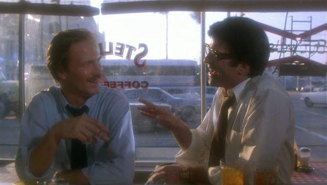 Ned Racine im Gespräch mit Peter Lowenstein vor einer großen Glasscheibe in einem Diner.