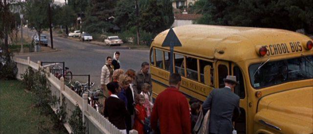 Ein gelber Schulbus hält am Straßenrand, wo Kinder und einige Eltern warten.