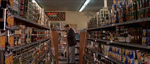 Blick durch die Schneise zweier gefüllter Regalreihen eines Supermarktes; am Ende steht Larry Coe beim Einkauf.