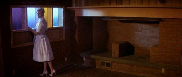 Maggie steht am Fenster in einem dunklen Raum des neuen Hauses.