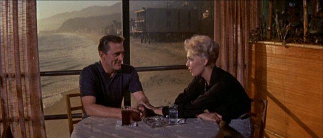 Romantisches Beisammensein von Larry und Maggie an einem Tisch eines Strandrestaurants.