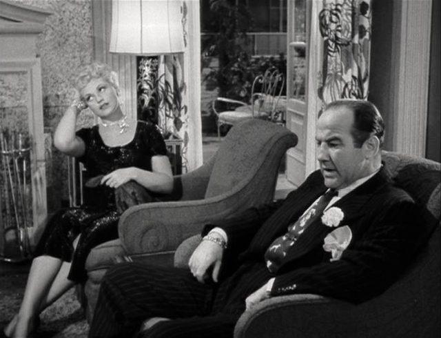 Billie Dawn mit gelangweiltem Blick in einem Sessel, in einem benachbarten Sessel Harry Brock mit angestrengter Mimik.