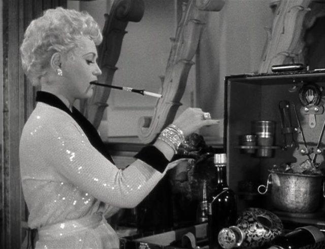 Billie Dawn mixt sich mit langem Zigarettenhalter im Mund einen Drink, vor ihr eine Schatulle mit Equipment und Zutaten.